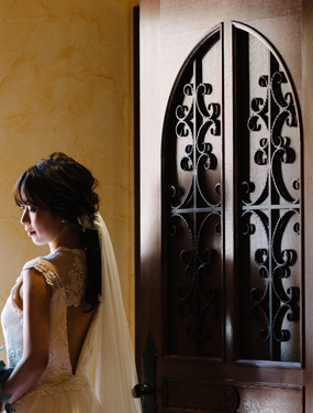 Bride waiting for her chapel entrance near a wooden door
